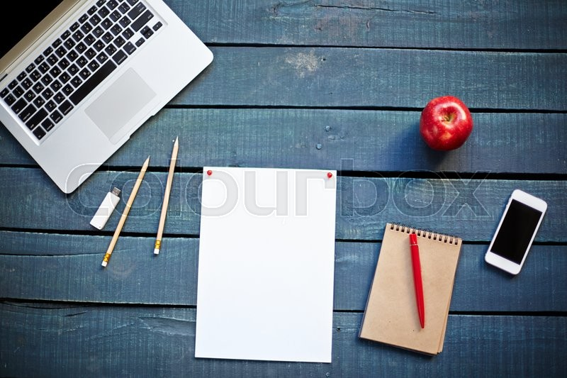 Close-up of laptop, papers and cellphone on wooden table, stock photo