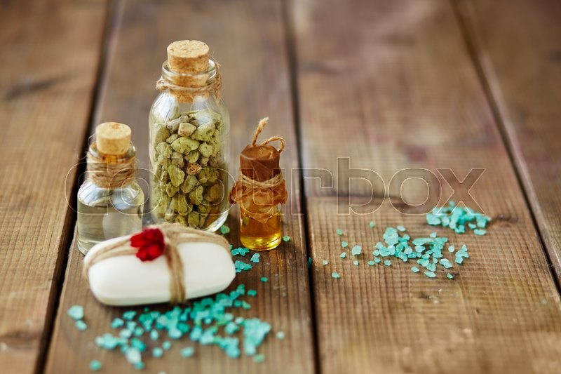 Soap bar bound by thread, sea salt and bottles with spa aromas, stock photo