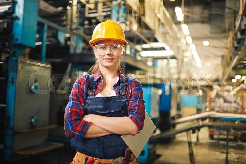 Portrait of young woman in protective glasses in the factory, stock photo