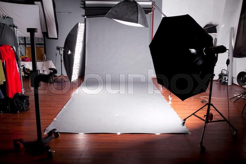Empty photo studio with lighting equipment, Dark studio with grey background, stock photo