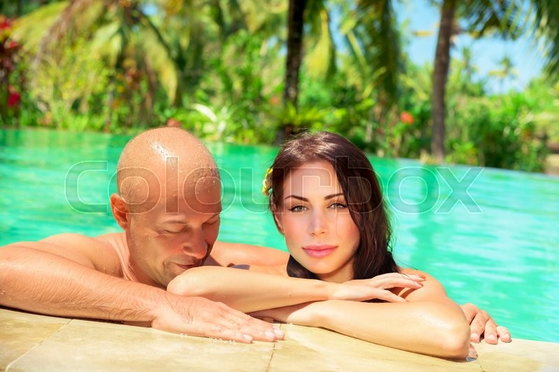 Portrait of a happy couple enjoying swimming pool for Tropical vacations for couples