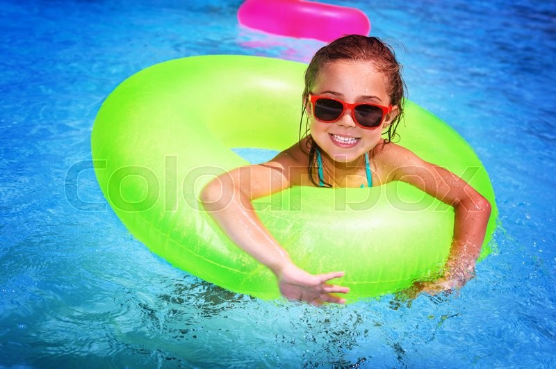 Portrait of cute happy little girl having fun in swimming pool, floating in blue refreshing water with big green rubber ring, active summer vacation on the beach, stock photo