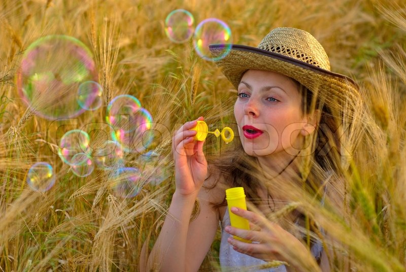 Stock image of 'Girl in wheat field in white dress and stetson hat  blowing soap bubbles. Selective focus.'