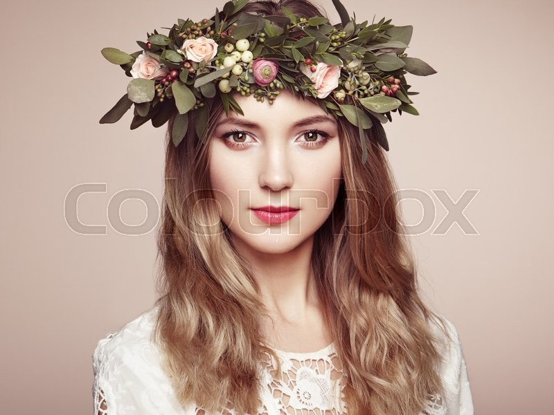 Beautiful blonde woman with flower wreath on her head. Beauty girl with flowers hairstyle. Perfect makeup. Beauty fashion. Spring woman, stock photo