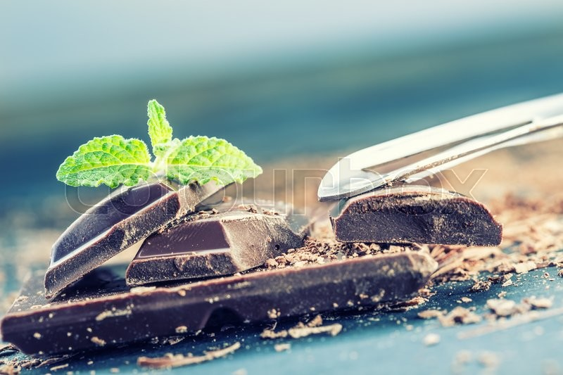 Chocolate. Black chocolate. A few cubes of black chocolate with mint leaves. Chocolate slabs spilled from grated chockolate powder, stock photo