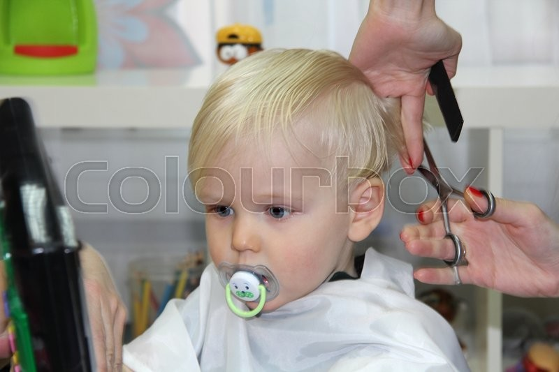 blonde little boy cut their hair in a childrens. Black Bedroom Furniture Sets. Home Design Ideas