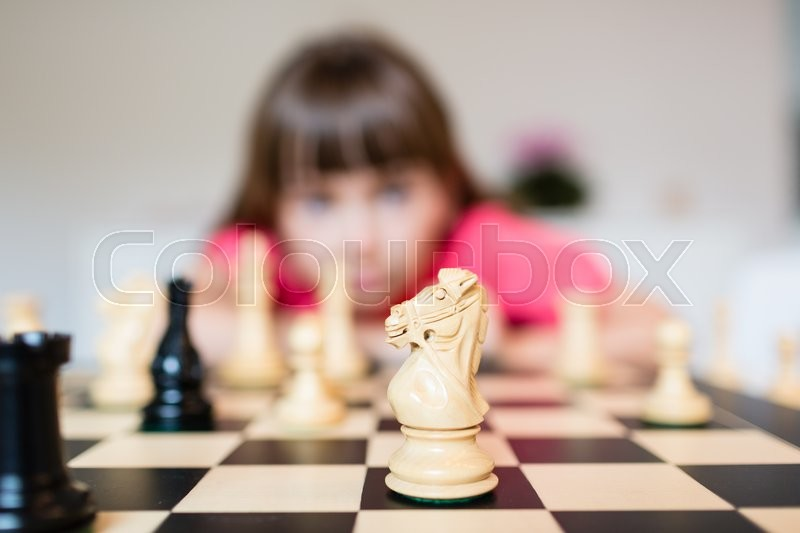 Young white child playing a game of chess on large chess board, stock photo