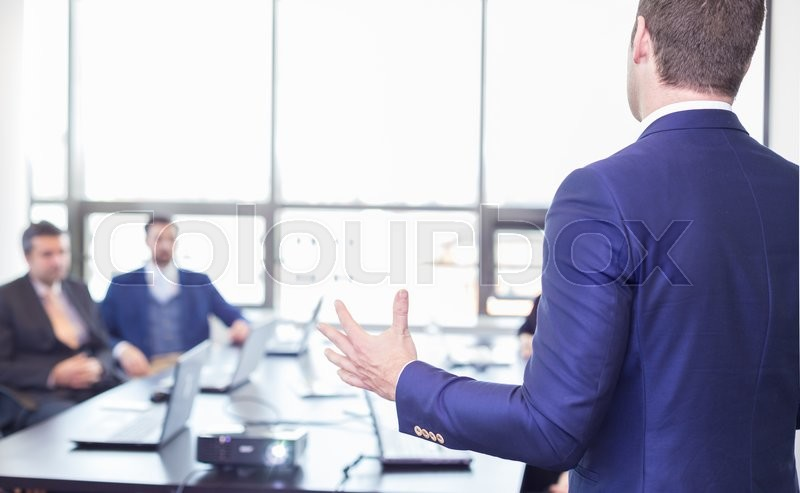 Business man making a presentation in office. Business executive delivering a presentation to his colleagues during meeting or in-house business training, explaining business plans to his employees. , stock photo