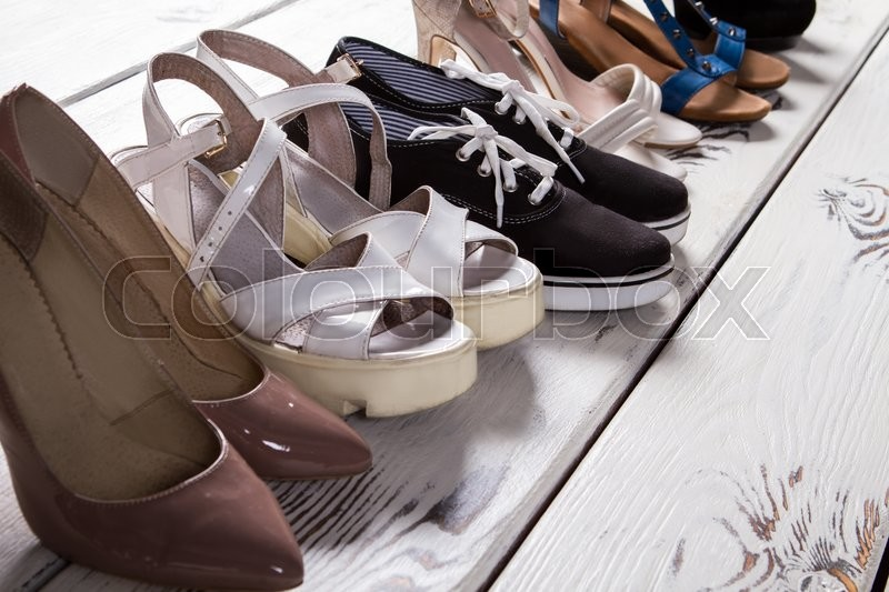 Lady\'s different shoes in row. Woman\'s footwear on boutique floor. Summer shoes of high quality. Luxury shoes and simple keds, stock photo