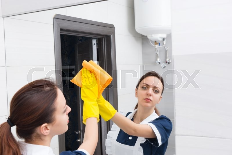 Serious Young Female Maid Wearing Rubber Gloves Looking In Mirror While Cleaning Bathroom With