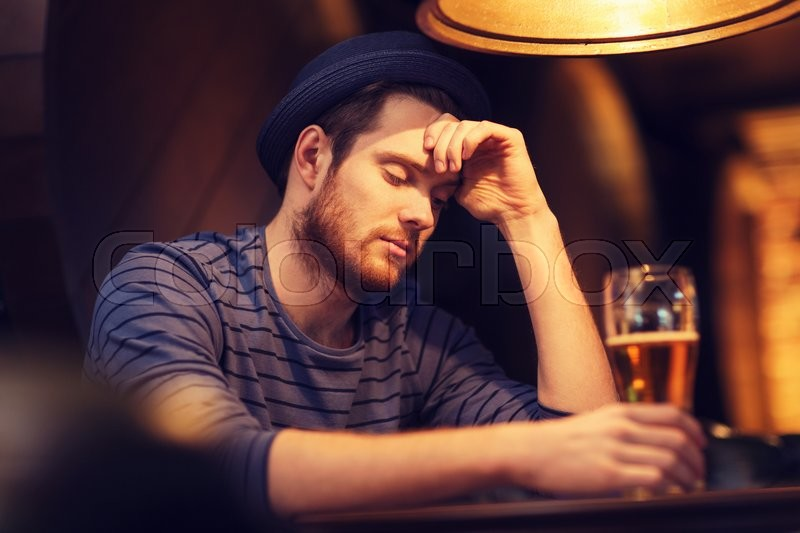 People, loneliness, alcohol and lifestyle concept - unhappy single young man in hat drinking beer at bar or pub, stock photo