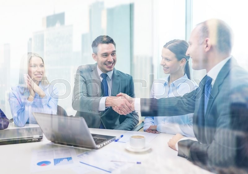 Business, technology and office concept - two smiling businessman shaking hands in office, stock photo