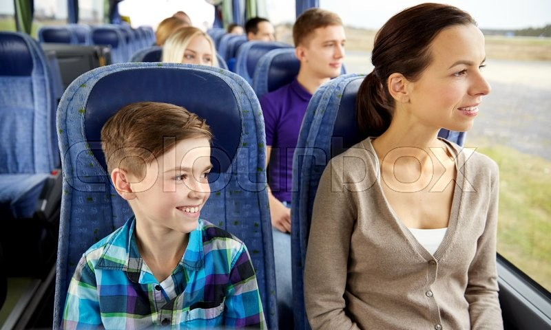 Travel, tourism, family, technology and people concept - happy mother and son riding in travel bus, stock photo