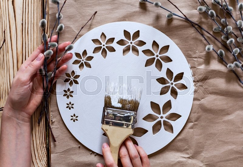 Master Class. Watch handmade. Step by step instructions for the manufacture of clocks. Hands with paint brush base clock of white paint. Willow branches against the backdrop of kraft paper, stock photo