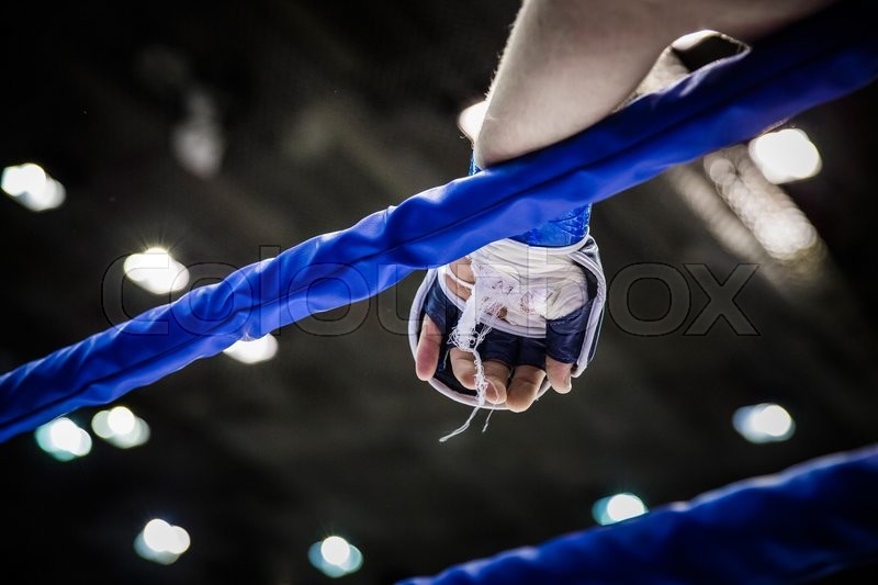 Hand of fighter on ropes of ring during competition in mixed martial arts, stock photo