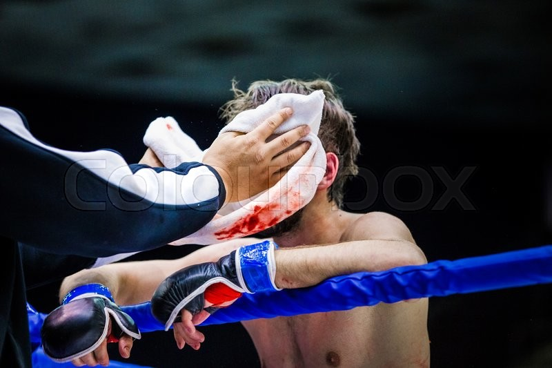 Cornerman wipes face of a fighter in between rounds, blood on towel, stock photo