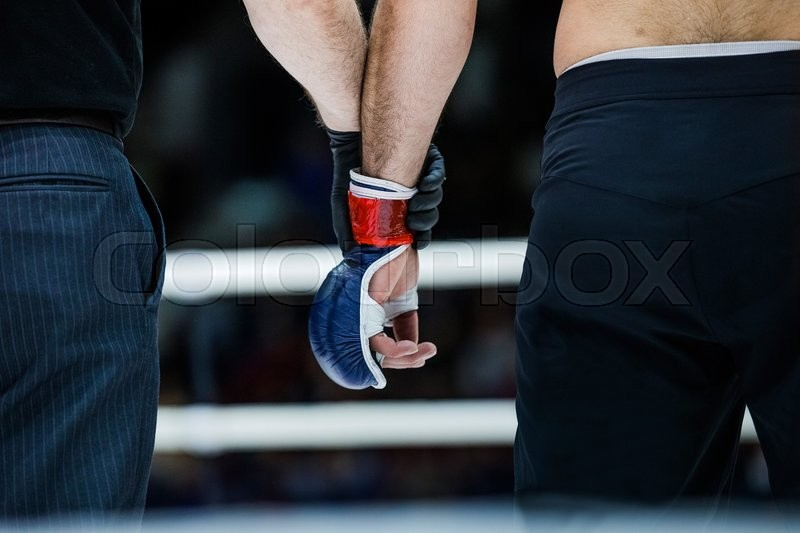Judge holds hand of boxer before announcing winners in a fight, stock photo