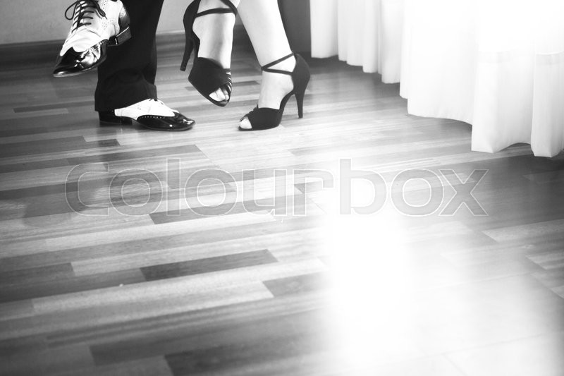 Male and female ballroom, standard, sport dance, latin and salsa couple dancers feet and shoes in dance academy school rehearsal room dancing salsa, stock photo
