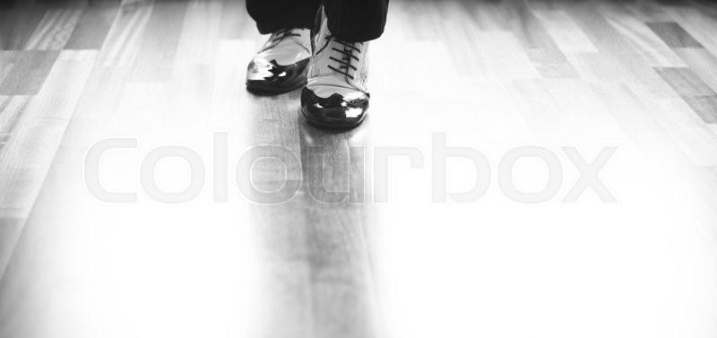 Male ballroom, standard, sport dance, latin and salsa dancer feet and shoes in dance academy school rehearsal room dancing salsa, stock photo