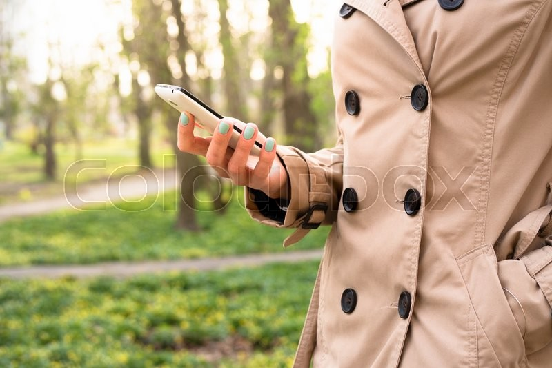 Woman in beige coat walks in the park and using a mobile phone, stock photo