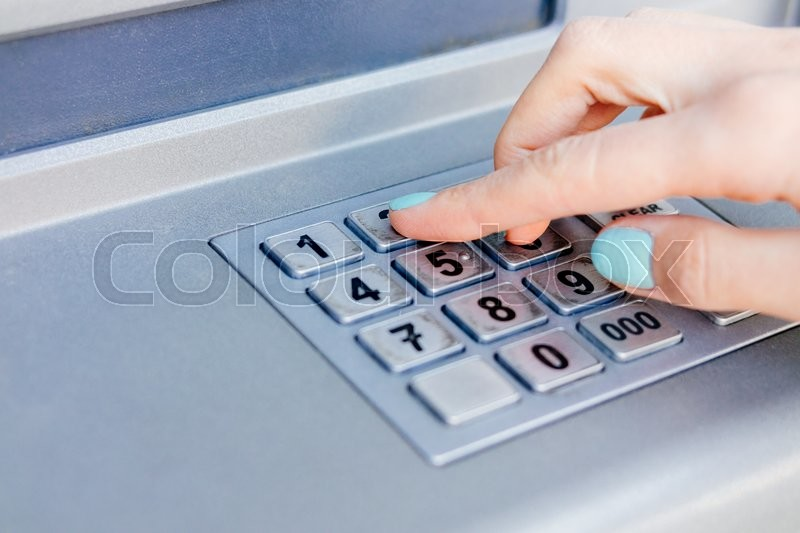 Ladies hand dials the PIN code at an     | Stock image