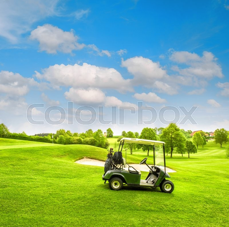 Green golf course field and cloudy blue sky. Spring landscape with fresh grass. Vibrant colors, stock photo