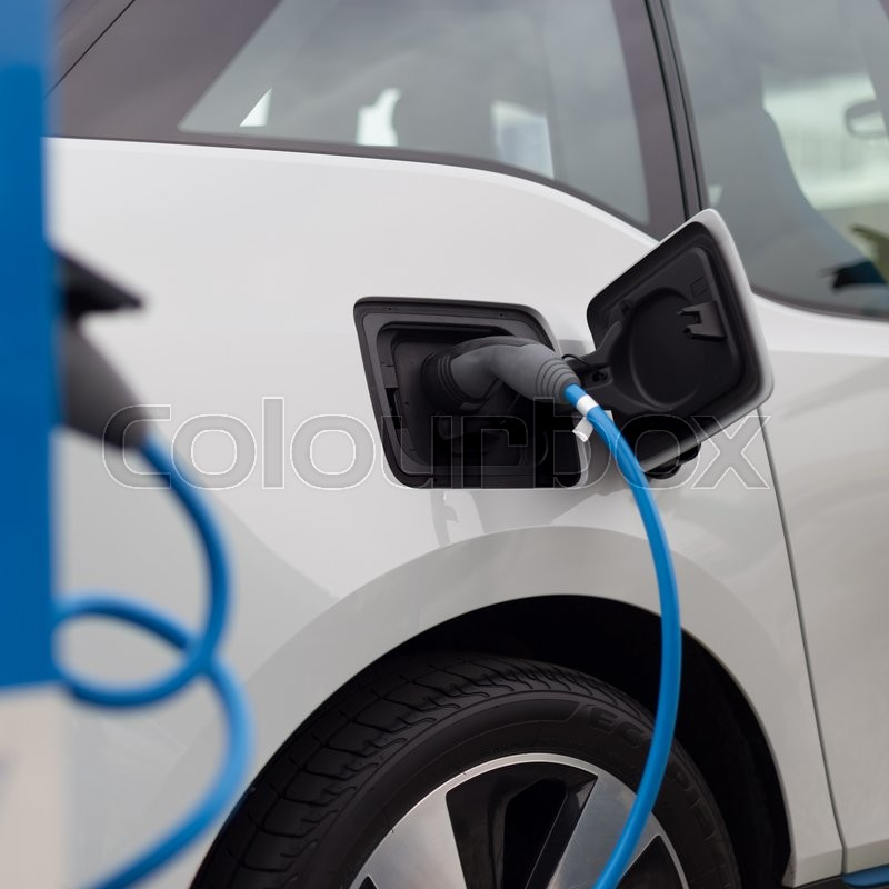 Power supply for electric car charging. Electric car charging station. Close up of the power supply plugged into an electric car being charged, stock photo