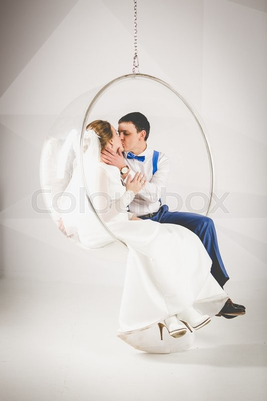 Just married young couple kissing in plastic bubble chair | Stock Photo |  Colourbox
