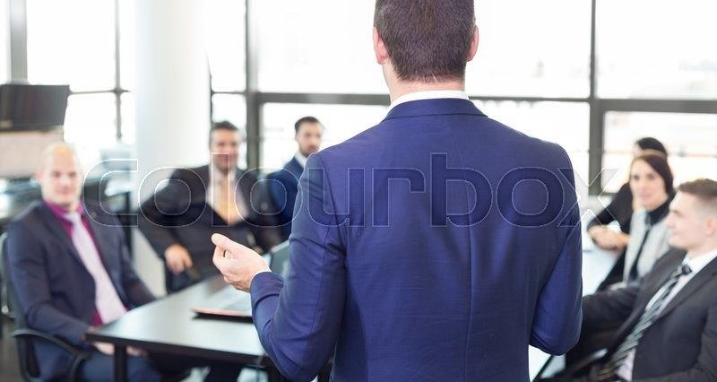 Successful team leader and business owner leading informal in-house business meeting. Businessman working on laptop in foreground. Business and entrepreneurship concept, stock photo