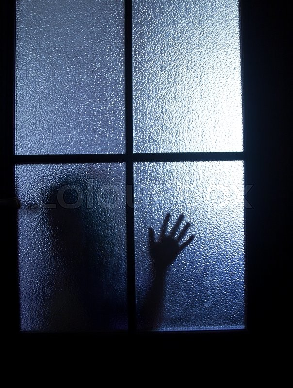 Blurred Silhouette Of A Child Behind A Glass Door In The Darkness