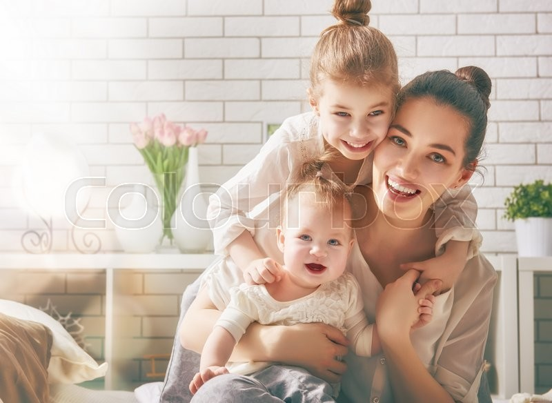 Happy loving family. Mother and her daughters children girls playing and hugging, stock photo
