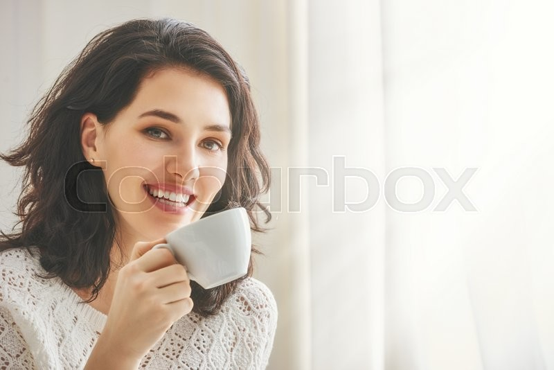 Beautiful young woman drinking coffee sitting by the window in the house, stock photo