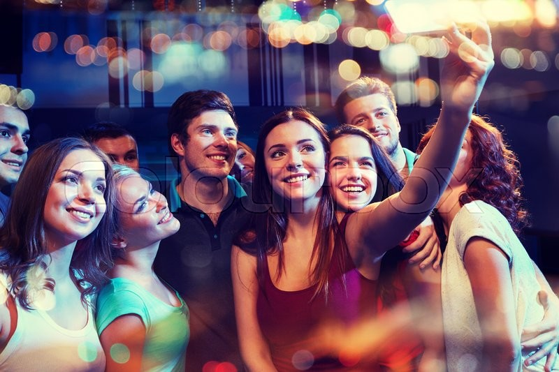 Party, technology, nightlife and people concept - smiling friends with smartphone taking selfie in club, stock photo