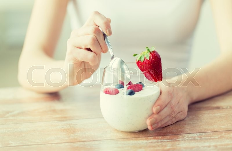 Healthy eating, vegetarian food, diet and people concept - close up of woman hands with yogurt and berries on table, stock photo