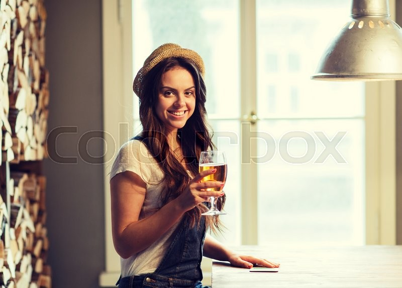 People, drinks, alcohol and leisure concept - happy young redhead woman drinking beer at bar or pub, stock photo