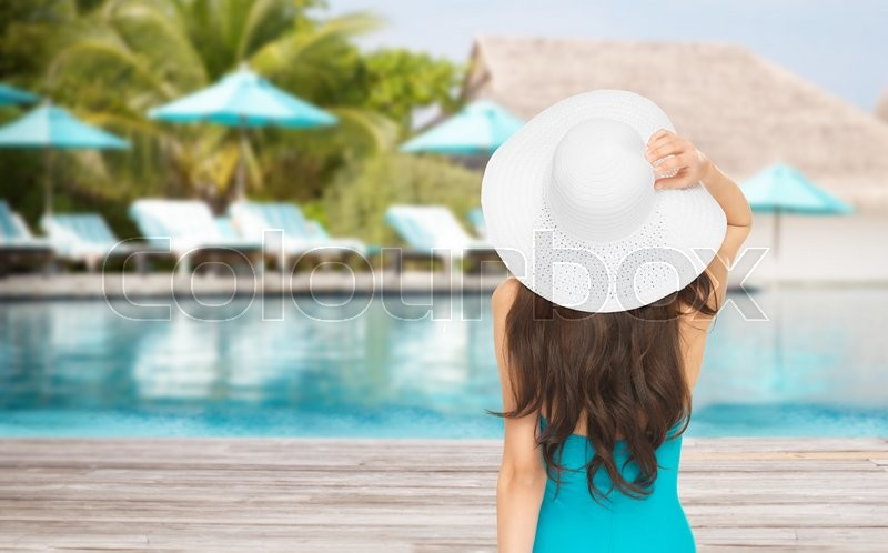 People, summer holidays, travel, tourism and vacation concept - woman in swimsuit and sun hat from back over exotic hotel resort beach with swimming pool and sunbeds background, stock photo