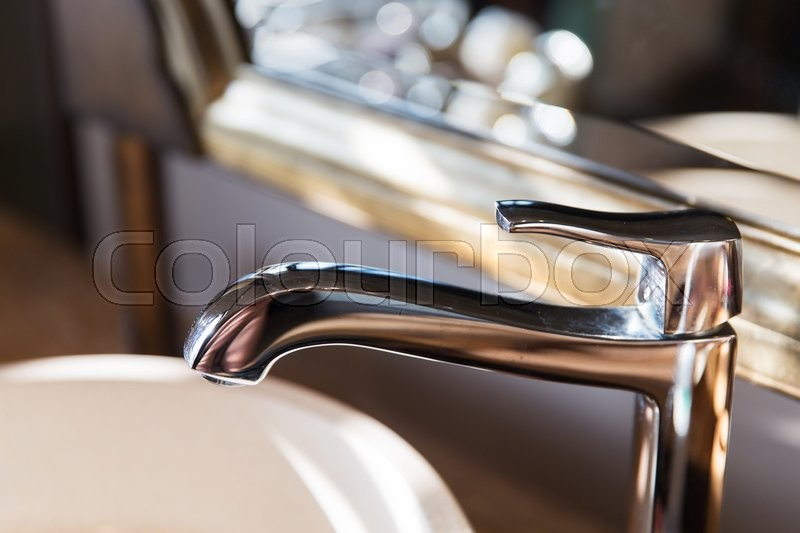 Sanitary, plumbing and washing concept - close up of bath tap or faucet at bathroom, stock photo