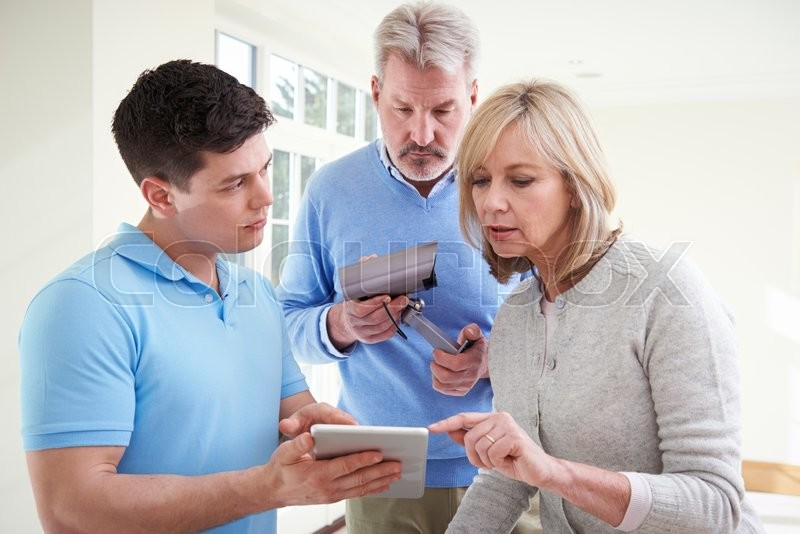 Security Consultant Demonstrating Alarm System To Mature Couple, stock photo