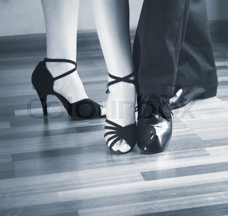 Male and female ballroom, standard, sport dance, latin and salsa couple dancers feet and shoes in dance academy school rehearsal room dancing modern contemporary style, stock photo