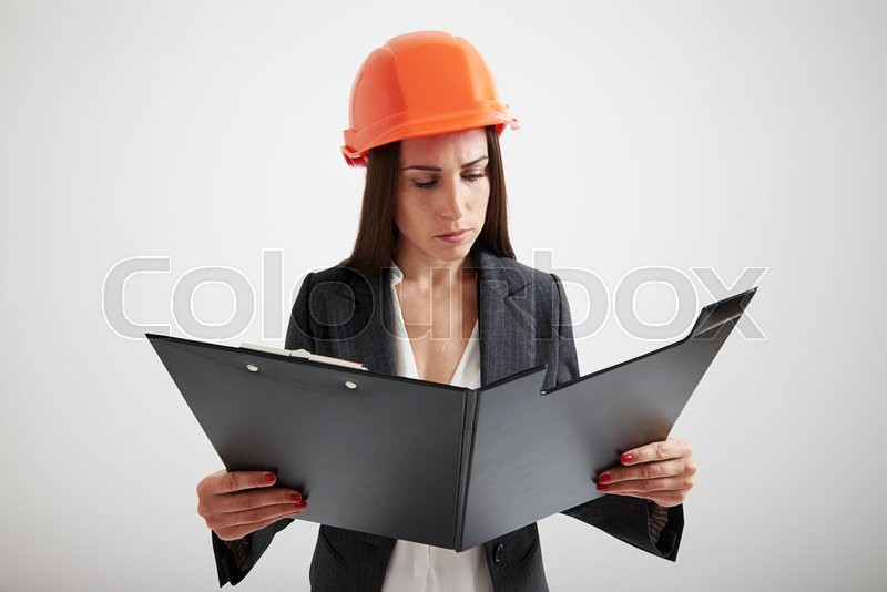 serious woman in formal wear and hard hat familiarize with the