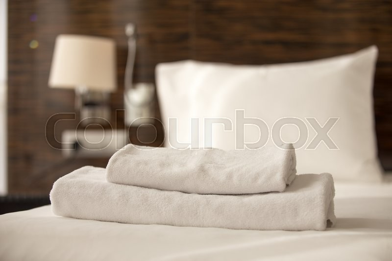 Stacked clean white bath towels on the bed sheets in hotel room, close-up, stock photo