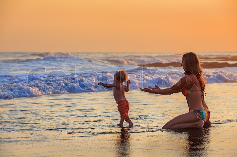 Family swimming fun in sea beach surf Happy mother, baby son first step - toddler run to ocean wave on sunset sky background Child outdoor activity, parent lifestyle, summer holiday in tropical island, stock photo