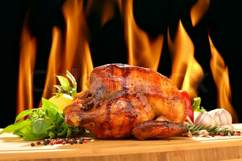 Roasted chicken and various vegetables on a chopping wood, stock photo