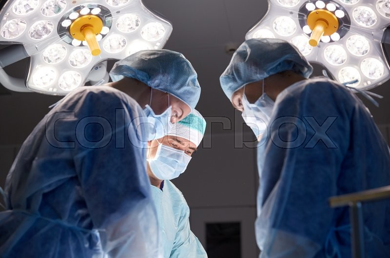 Surgery, medicine and people concept - group of surgeons at operation in operating room at hospital, stock photo