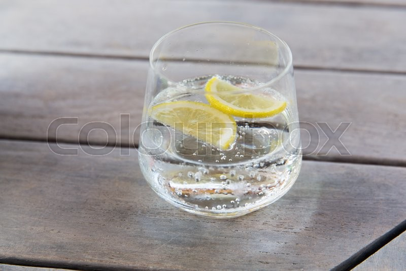 Drink and refreshment concept - glass of sparkling water with lemon slices on table, stock photo