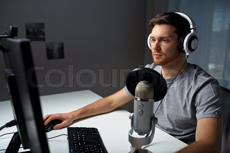 Technology, gaming, entertainment, let\'s play and people concept - young man in headset with pc computer playing game at home and streaming playthrough or walkthrough video, stock photo