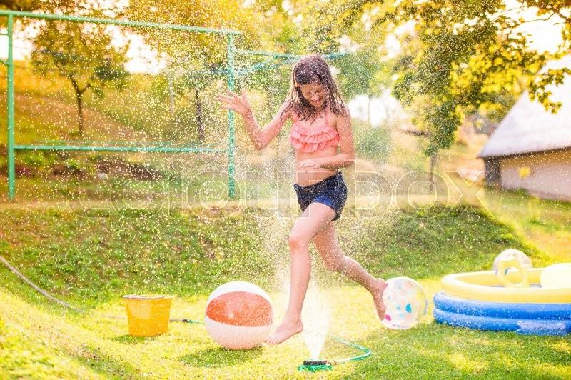 Girl running above a sprinkler, sunny summer back yard, garden swimming pool, stock photo