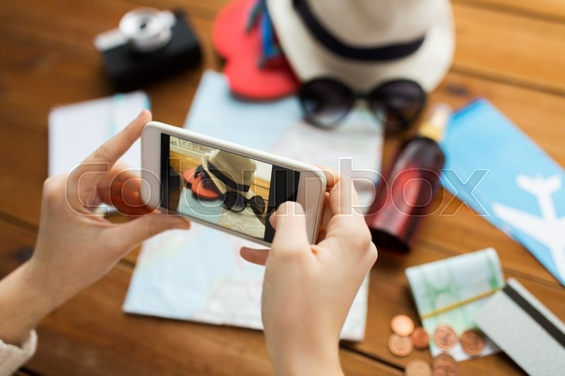 Vacation, tourism, travel, technology and people concept - close up of woman with smartphone photographing map and travel stuff, stock photo