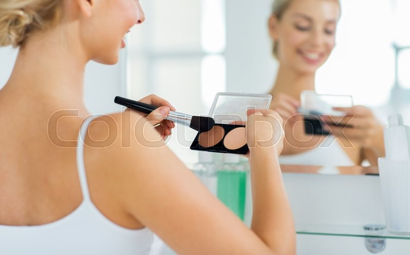 Beauty, make up, cosmetics, morning and people concept - close up of happy young woman with makeup brush and contouring and highlighting palette looking to mirror at home bathroom, stock photo