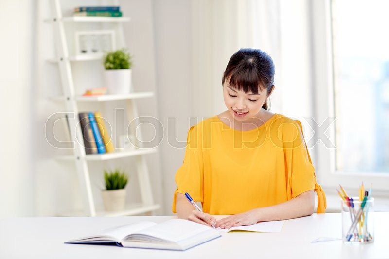 People, education, high school and learning concept - happy asian young woman student with book and notepad writing at home, stock photo